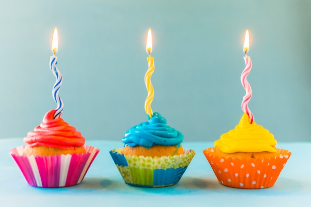 Row of cupcakes with burning candles on blue backdrop
