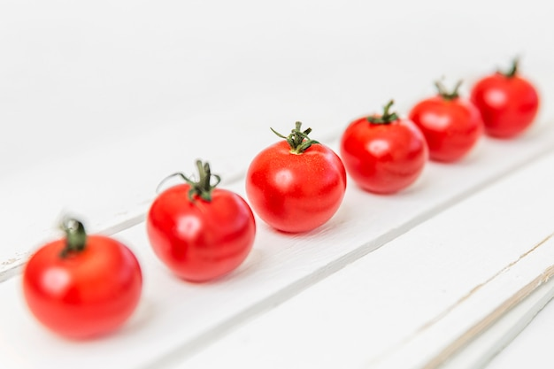 Row of delicious cherry tomatoes on a white wooden table. diagonal. healthy eating and vegetarianism. space for text.