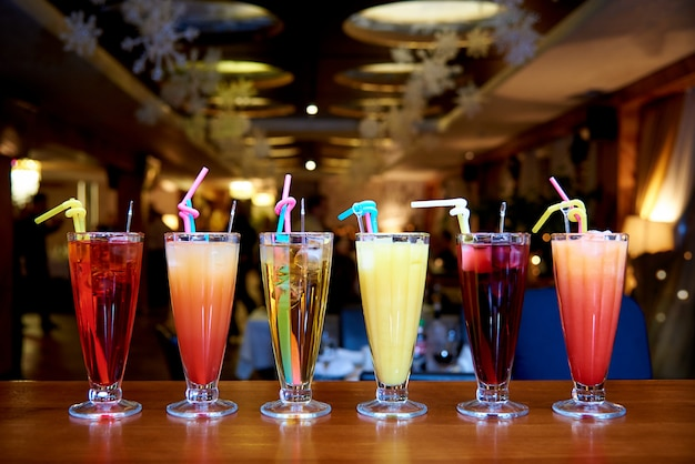Row of different cocktails with straws