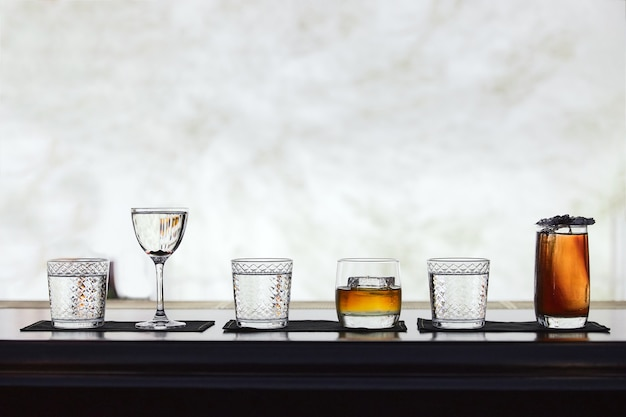 Row of different simple cocktail drinks, darker themes