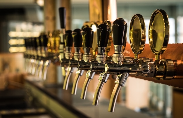 Row of draft beer tap on the top of counter bar in closeup view, time of celebration.