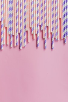 Row of drinking straws with stripe and polka dot design border on pink background.prohibition of the use of plastic.minimalism concept. pop art style.paper straws used for drinking water or soft