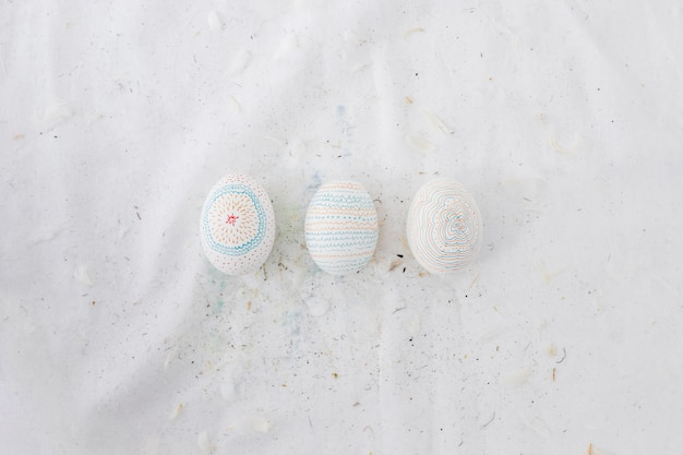 Row of easter eggs with patterns and feathers on textile