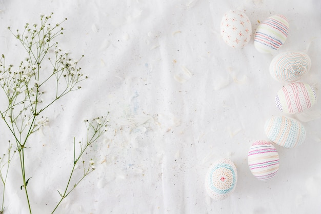 Row of easter eggs with patterns near plant twig and feathers on textile
