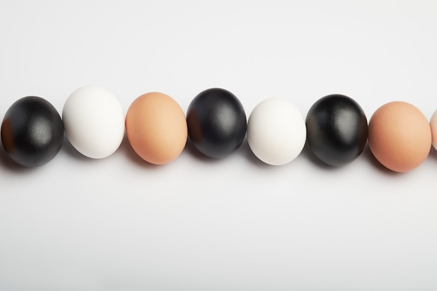 Row of eggs of different colors on a white background. black, white and brown chicken eggs.