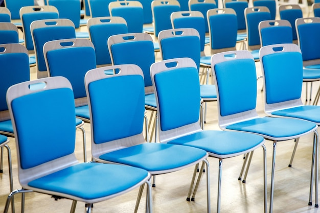 A row of empty blue chairs in the audience.