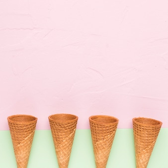 Row of empty ice cream cones on multicolored surface