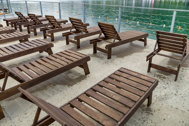 Row of empty wooden beach chairs near water.