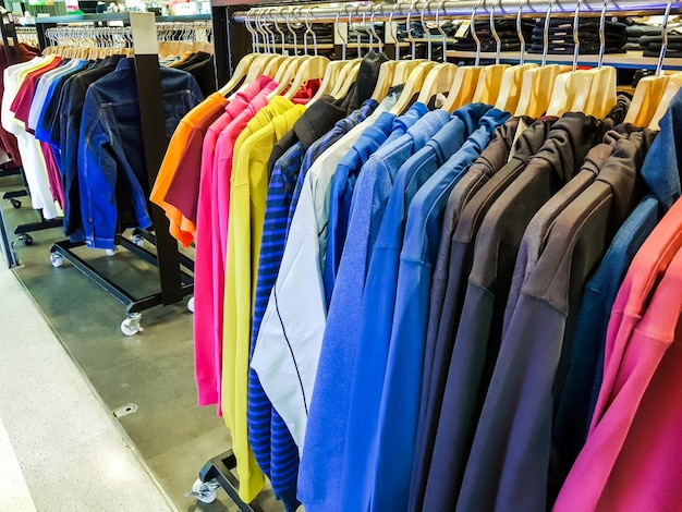 Row of fashionable clothing on hangers .
