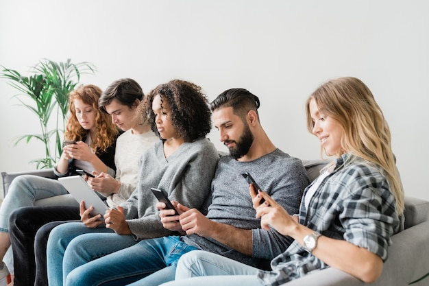 Row of five casual intercultural friendly millennials scrolling in their mobile gadgets while sitting on couch