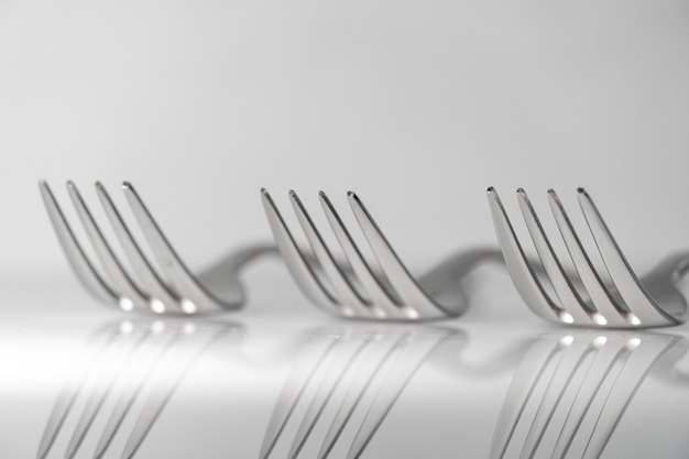 Row of forks on white marble texture background. concept for food and dining tableware