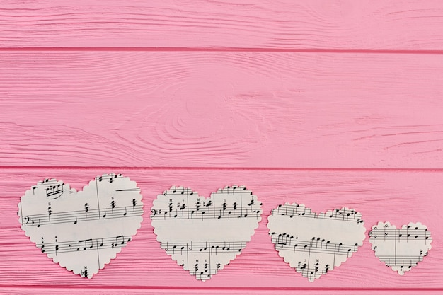 Row of four paper hearts with music notes.