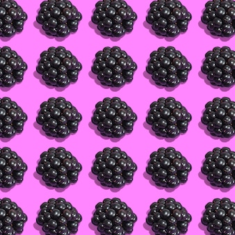 Row of fresh blackberries on pink background