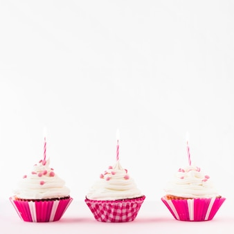 Row of fresh cupcakes with burning candles against white background