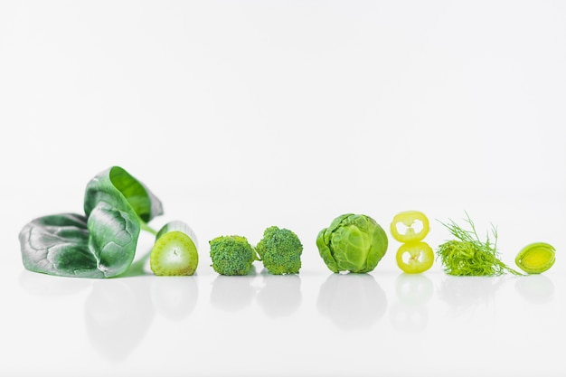 Row of fresh green vegetables on white background