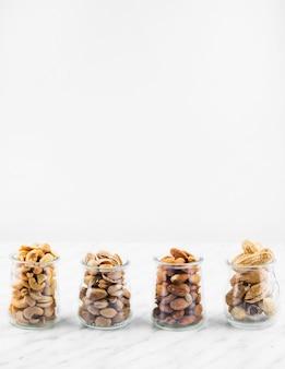 Row of fresh nut food jar on marble backdrop