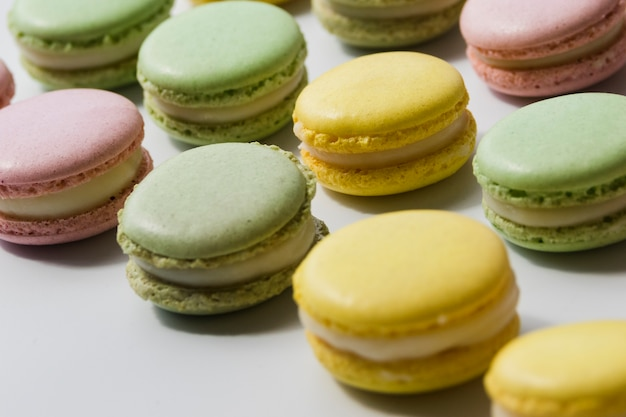 Row of fresh tasty macaroons on white backdrop