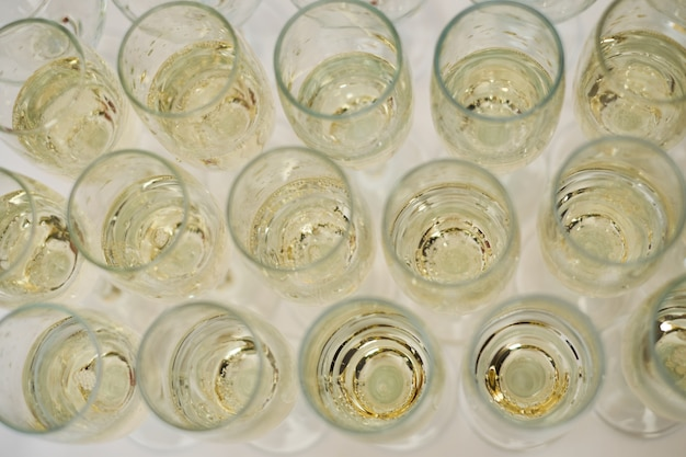 Row of glasses filled with cold champagne white wine white table