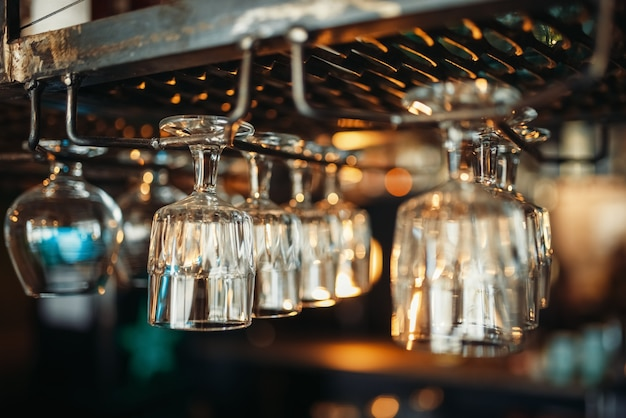 Row of glasses hanging on the bar counter closeup