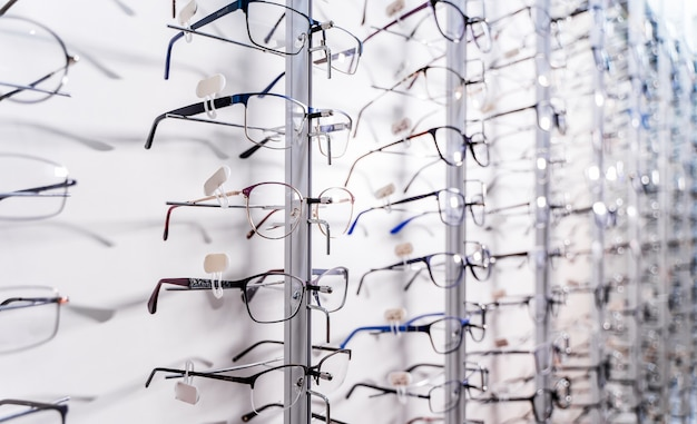 Row of glasses at an opticians. eyeglasses shop. stand with glasses in the store of optics. showcase with spectacles in modern ophthalmic store. closeup.