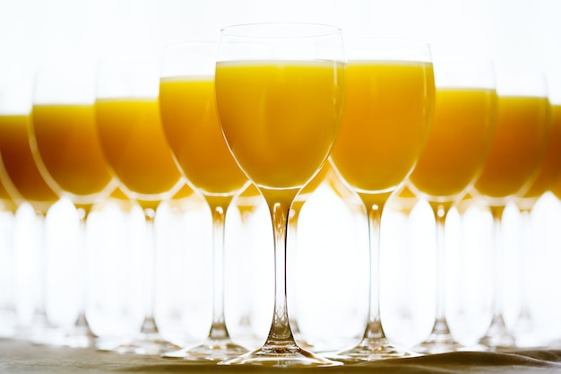 Row of glasses with fresh orange juice