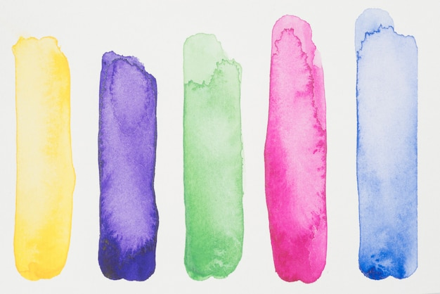 Row of green, pink, yellow and blue paints on white paper