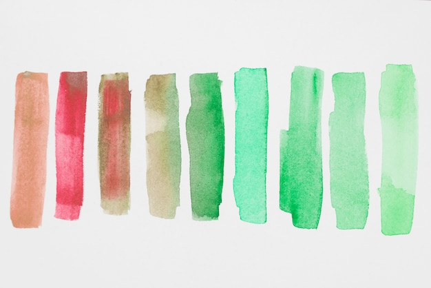 Row of green and red paints on white paper
