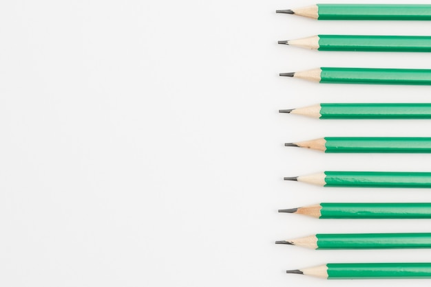 Row of green sharp pencils on white background