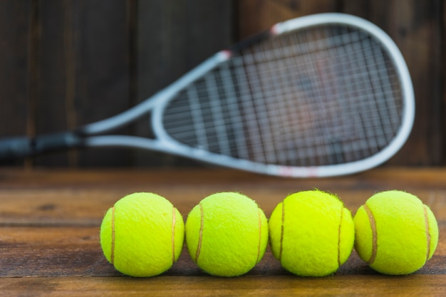 Row of green tennis balls in front of blurred racket on wooden table