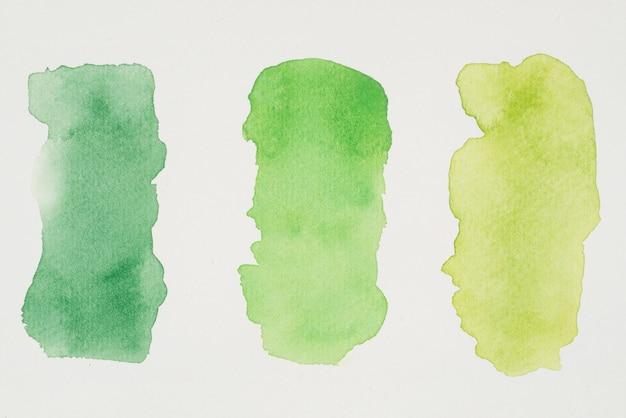 Fila di vernici verdi e gialle su carta bianca