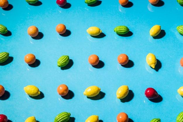 Row of gummy fruits shaped on blue background
