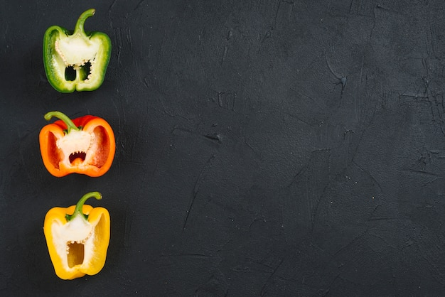 Row of halved bell peppers on black concrete backdrop