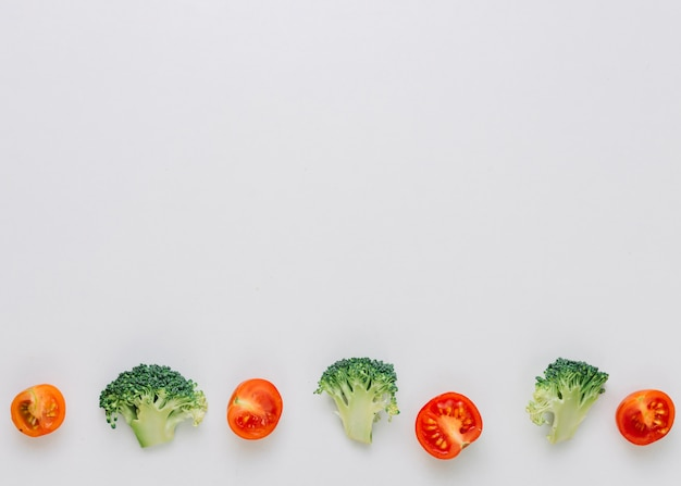 Row of halved cherry tomatoes and green broccoli on the bottom on white backdrop