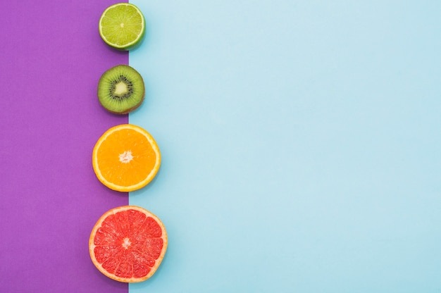 Row of halved citrus fruit and kiwi on dual background