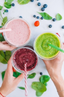Row of healthy fresh fruit and vegetable smoothies with assorted ingredients