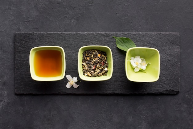 Row of healthy tea ingredient and white jasmine flower on slate stone