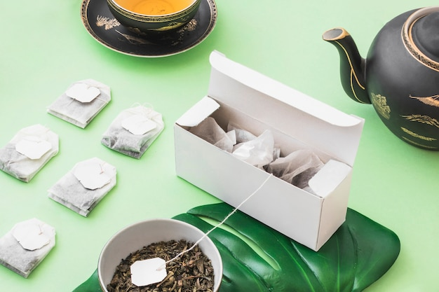Row of herbal tea bags with tea on green background
