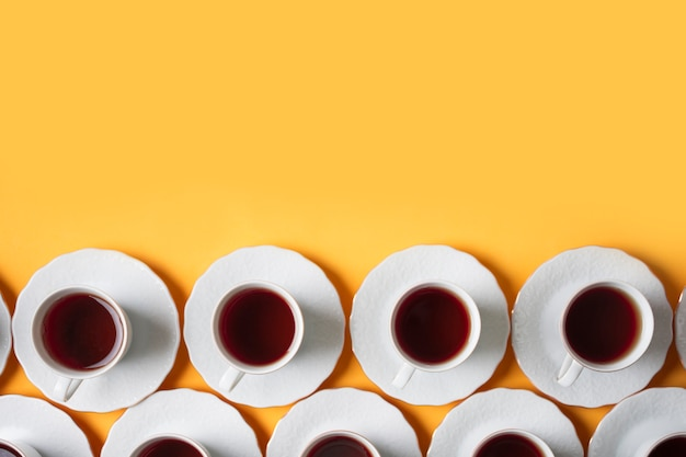 Row of herbal white tea cup on yellow background
