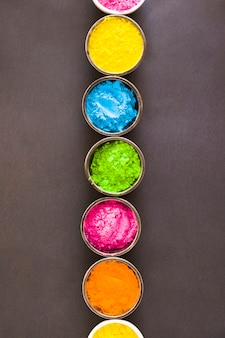 Row of holi color powder bowls against gray background