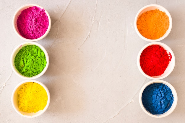 Row of holi color powder white bowls on textured backdrop