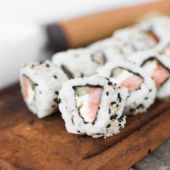 Row of homemade sushi on wooden tray