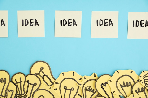 Row of idea adhesive notes over the border of many light bulbs against blue background