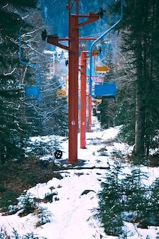 Row line of many pastel colored chairs of retro grunge ski lift, moving through winter pine forest covered in fresh snow in mountains, vertical shot
