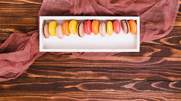 Row of macaroon in the white wooden box over the table