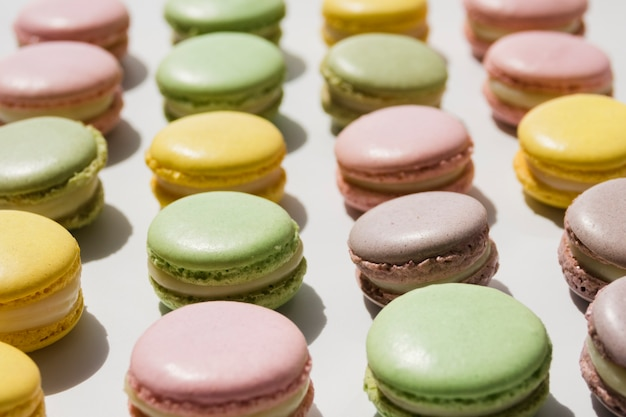 Row of macaroons arranged on white backdrop