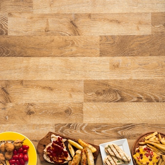 Row made of chicken fast food meal on wooden table