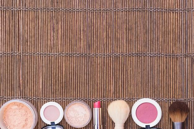 Row of makeup brush; blusher; loose powder on placemat