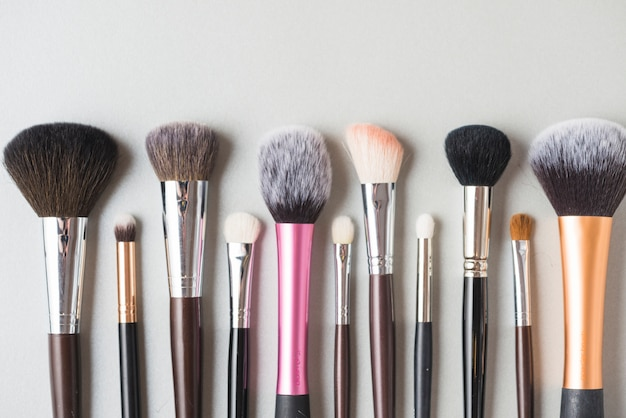 Row of makeup brushes on white surface