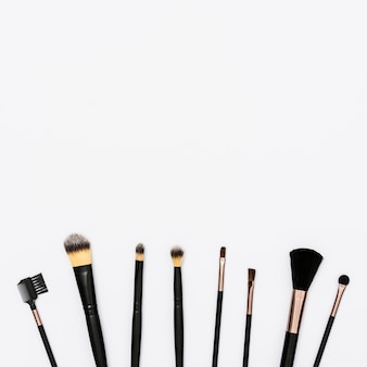 Row of makeup brushes with copy space for writing the text on white background