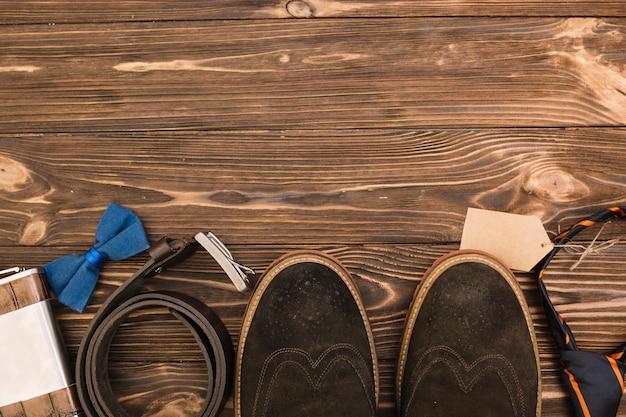 Fila di stivali maschili vicino ad accessori